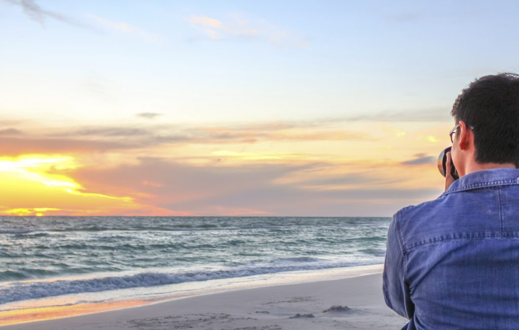 Young man photographs a beautiful sunset on the beach