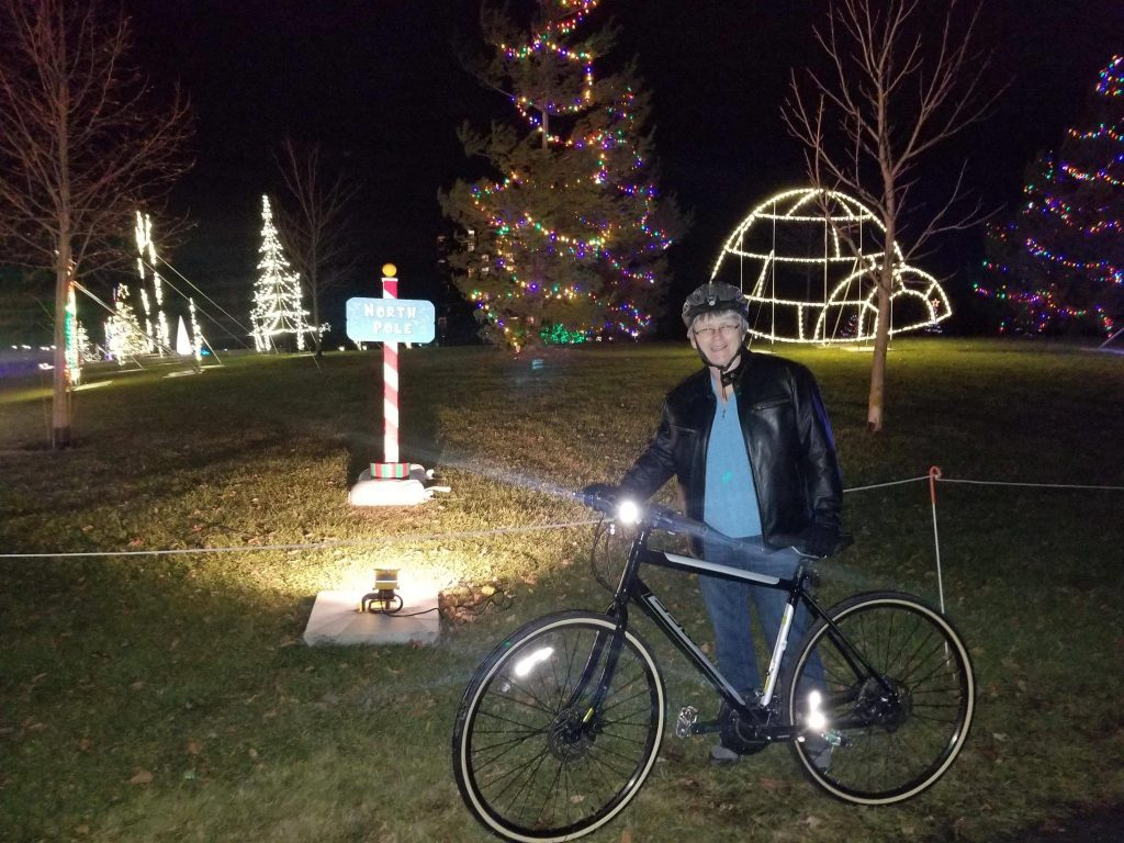 Donnah stands with her bike in front of some festive decorations