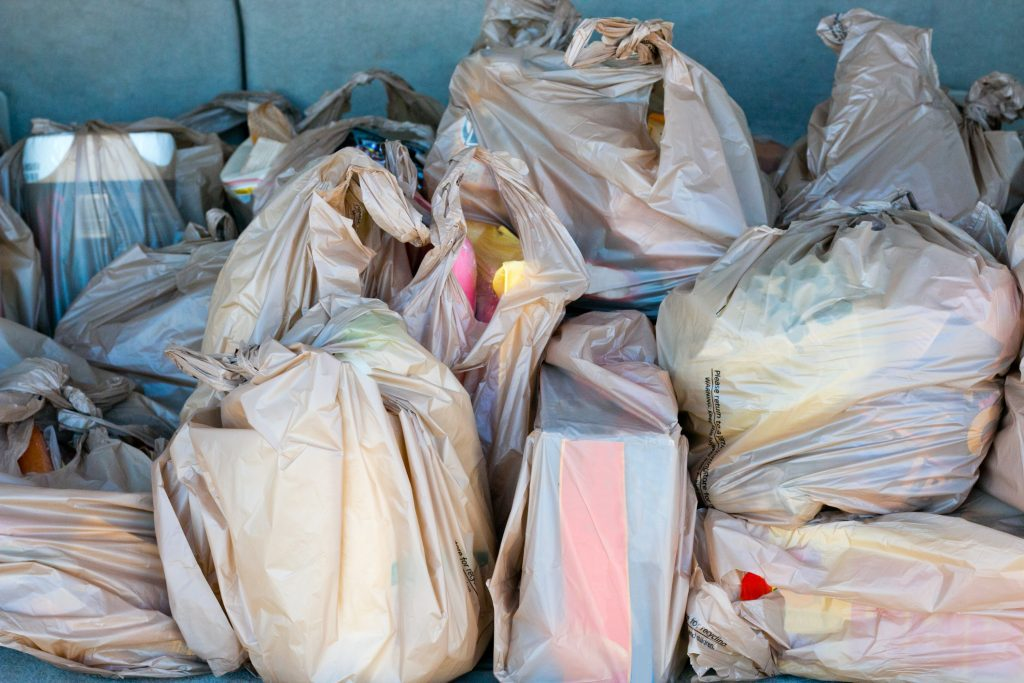 Plastic bags full of groceries in the trunk of a car